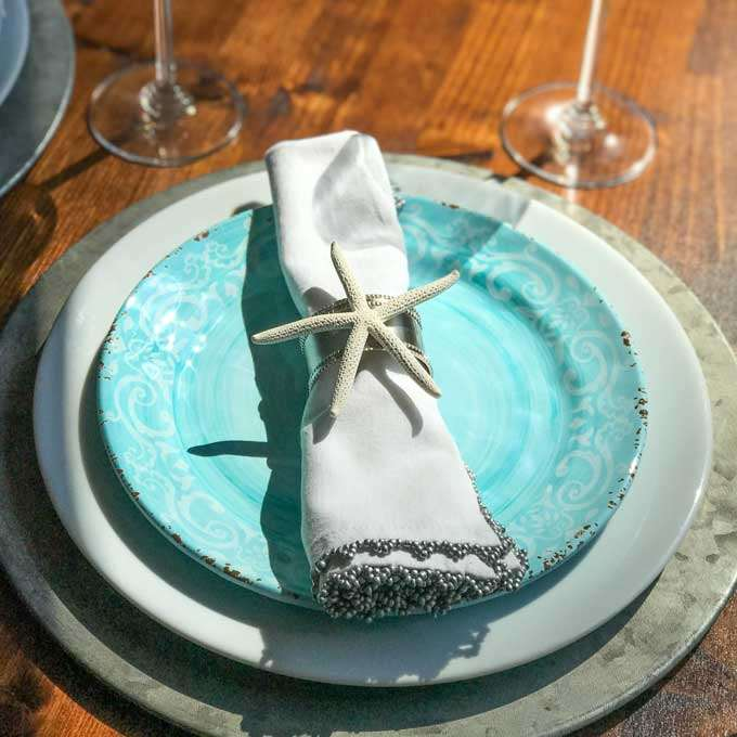 Coastal table top - starfish napkin ring, aqua and white plates, rustic metal charger