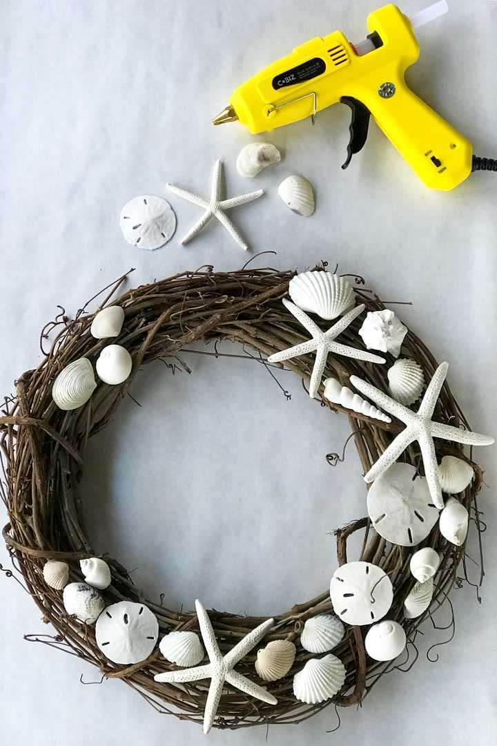 Making a seashell wreath with grape vine and shells and hot glue gun