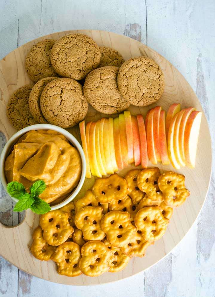 Ginger snaps, apple slices, pretzels, cream cheese dip on board