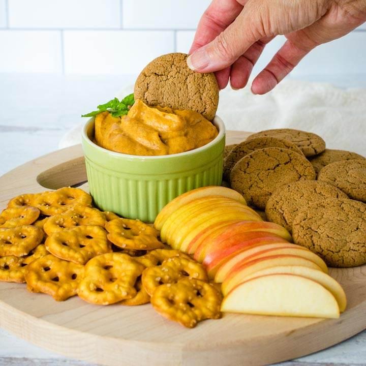 Dipping ginger snap in pumpkin dip