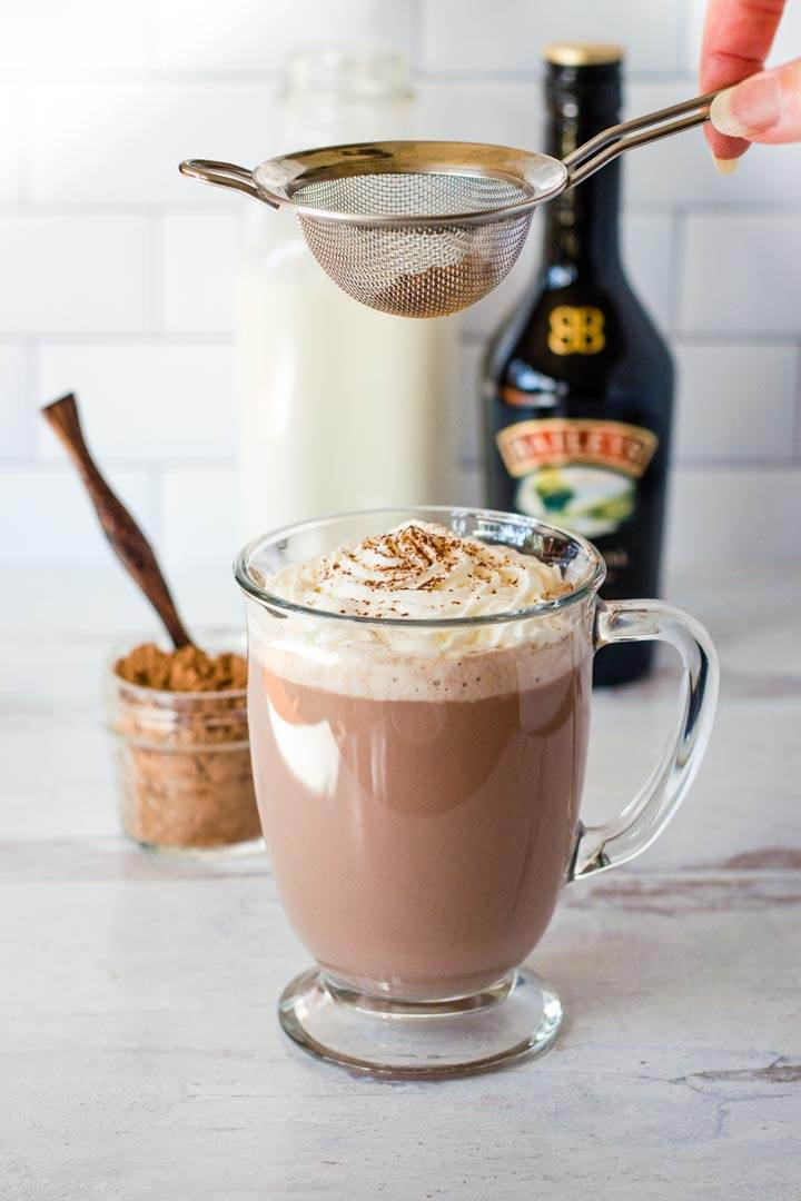 Sifting cocoa on whipped cream topping hot chocolate