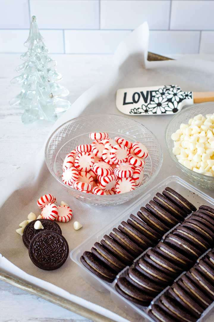 Oreo cookies, peppermint candies, white chocolate chips, and spatula on a baking sheet.