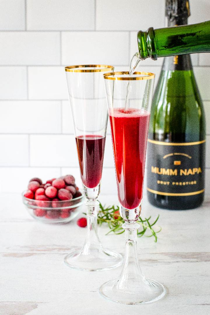 Champagne pouring into glass with pomegranate juice