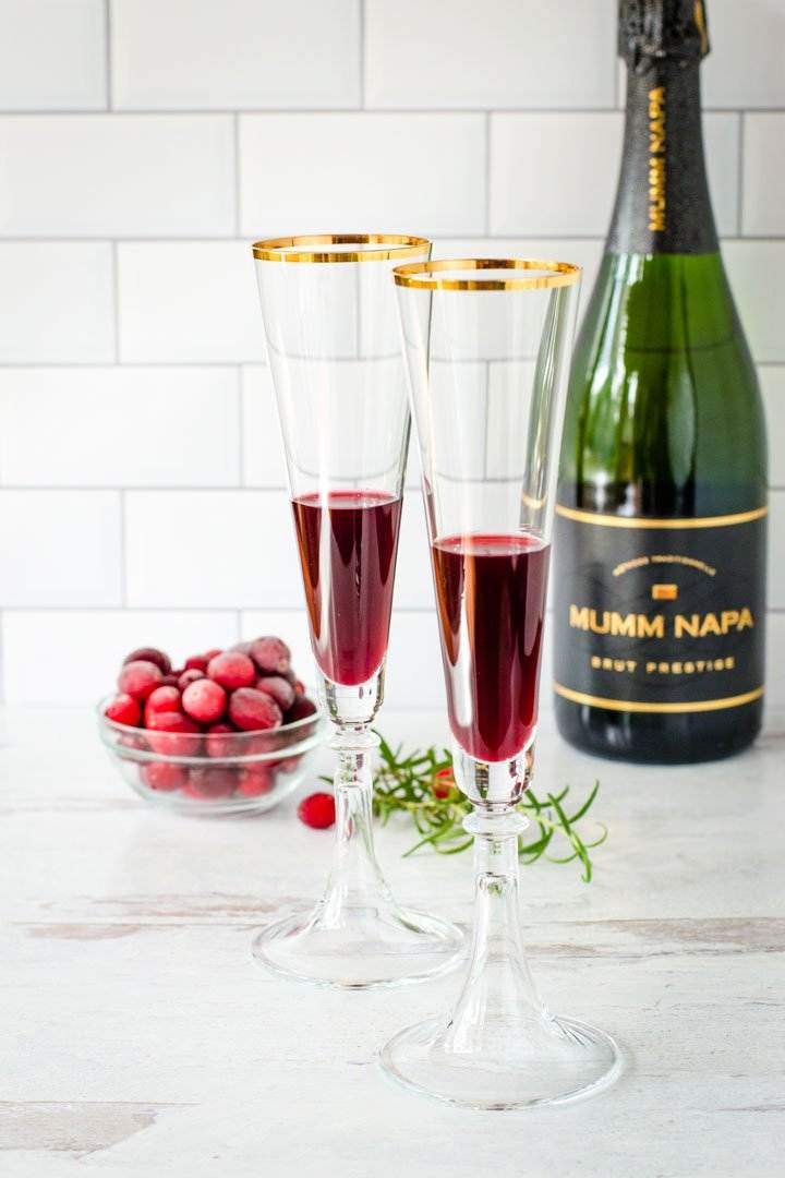 Pomegranate juice in flutes, champagne bottle, frozen cranberries, rosemary spring