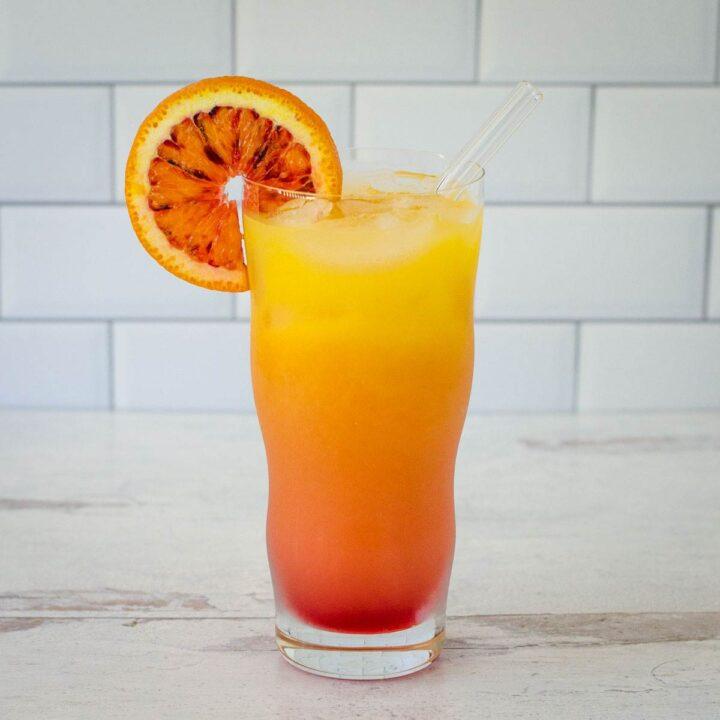 Vodka sunrise with orange slice and glass straw