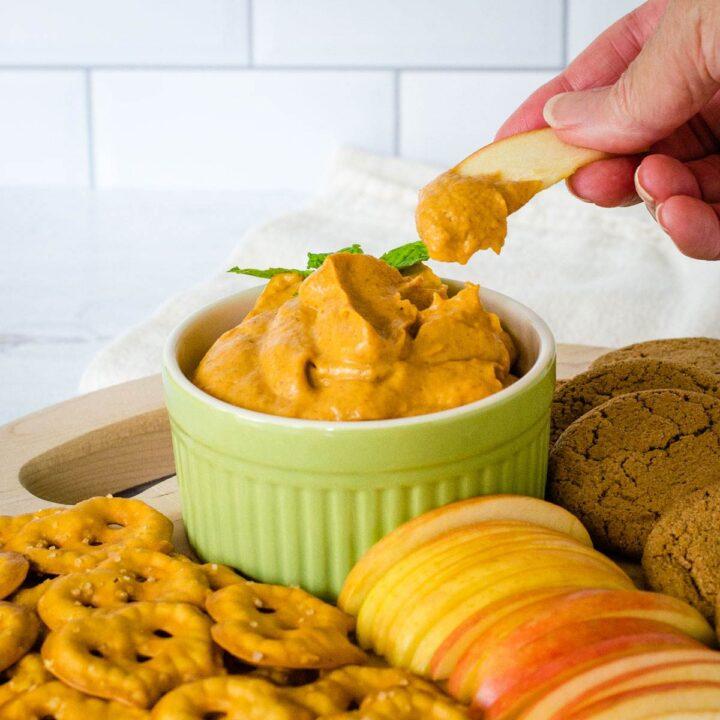 Dipping apple slice into pumpkin cream cheese dip